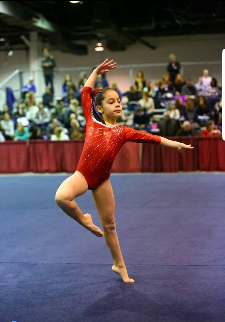 Melinda mid pose during a floor routine prior to her diagnosis (Photo courtesy of Facebook)