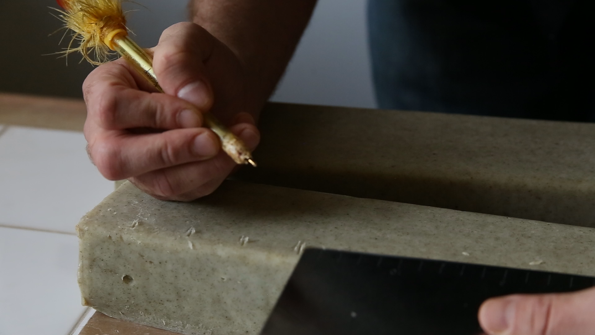 While still soft enough to cut easily, Shamus makes markings on the dried bar. (Ivana Rihter, 14 East Magazine)