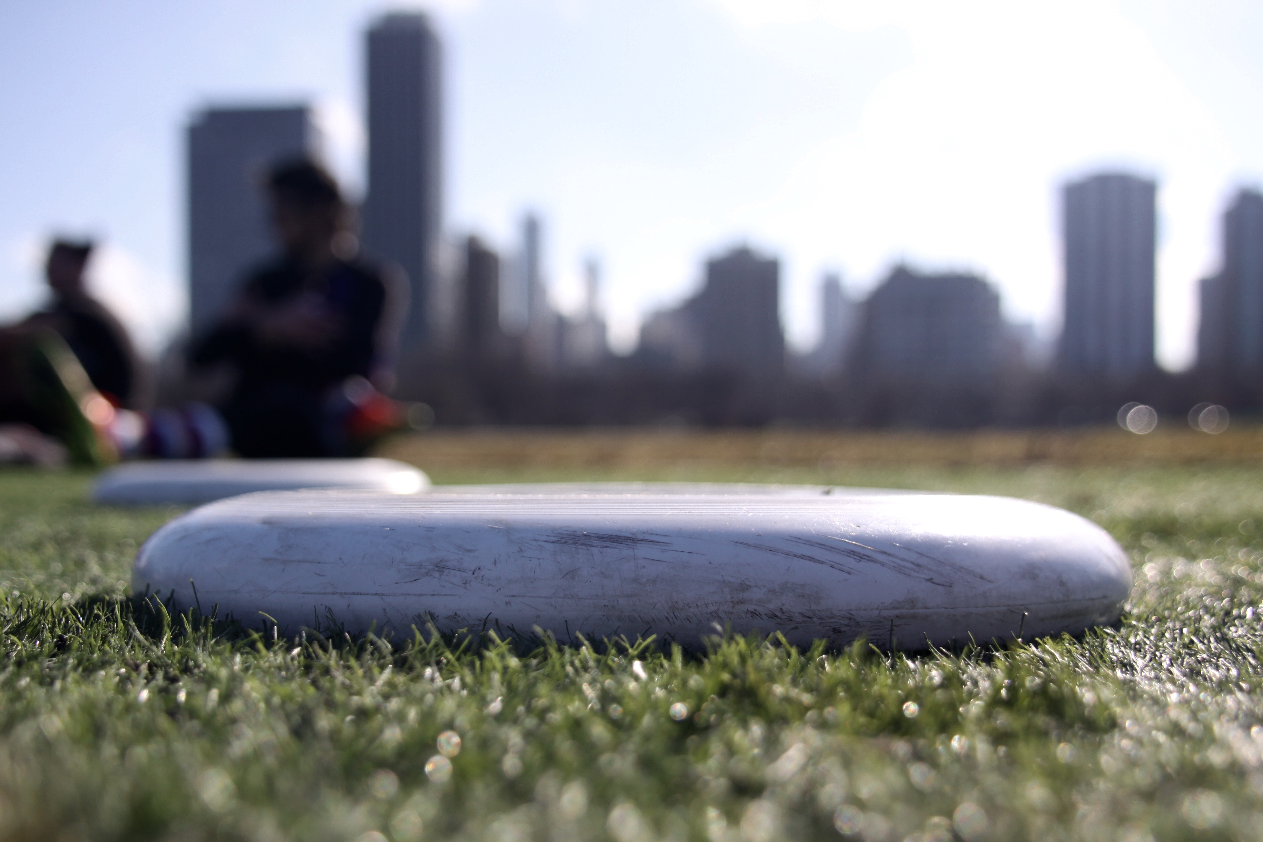 Sunshine highlights a severely scuffed Frisbee and the bright green turf at the end of a DePaul Ultimate Club practice on Jan. 21, 2017. (Photo/Ben Rains)