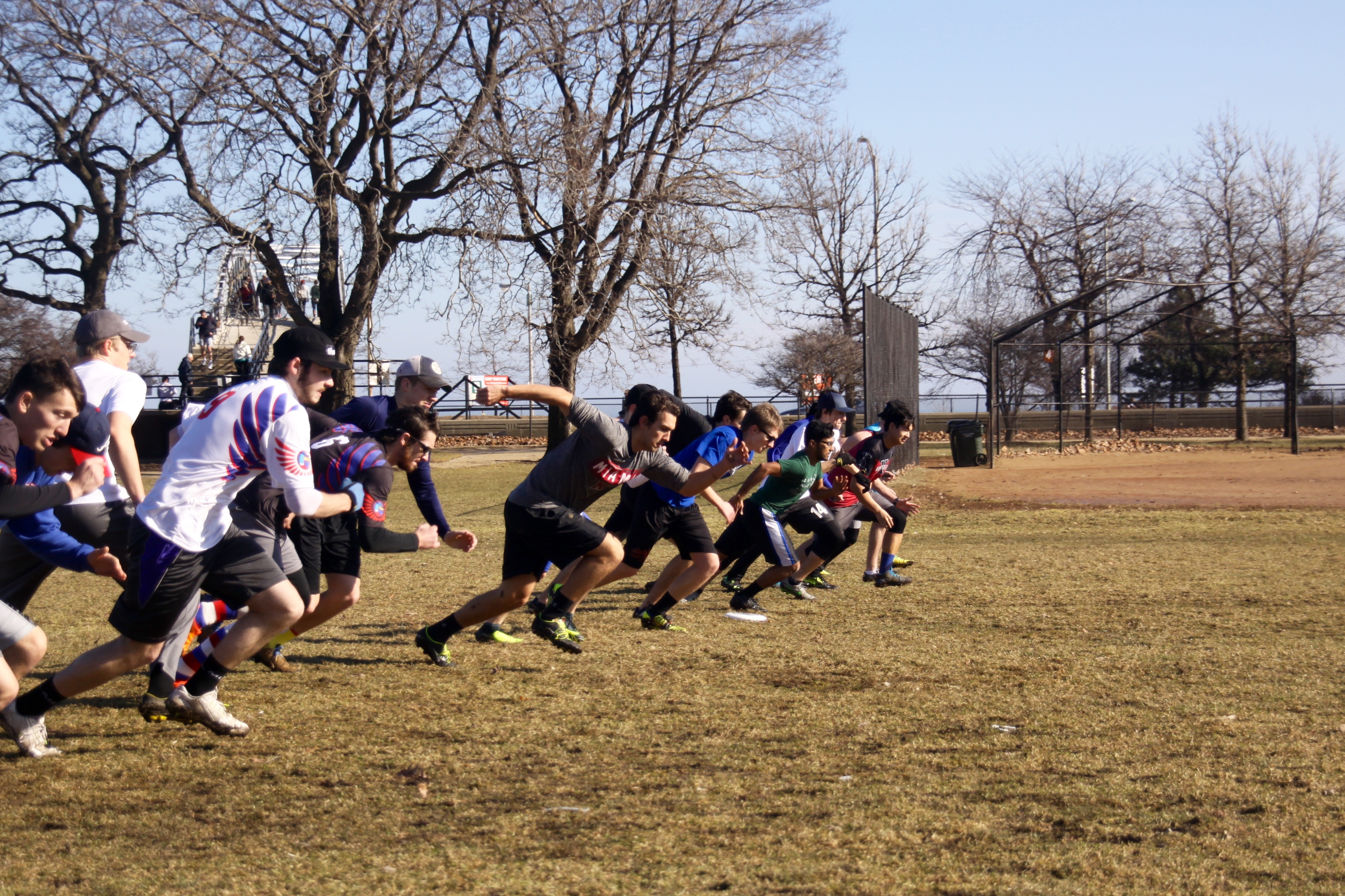 DePaul Ultimate Club members warm up by sprinting short distances during a sunny Saturday morning practice near Lake Michigan on Jan. 21, 2017.