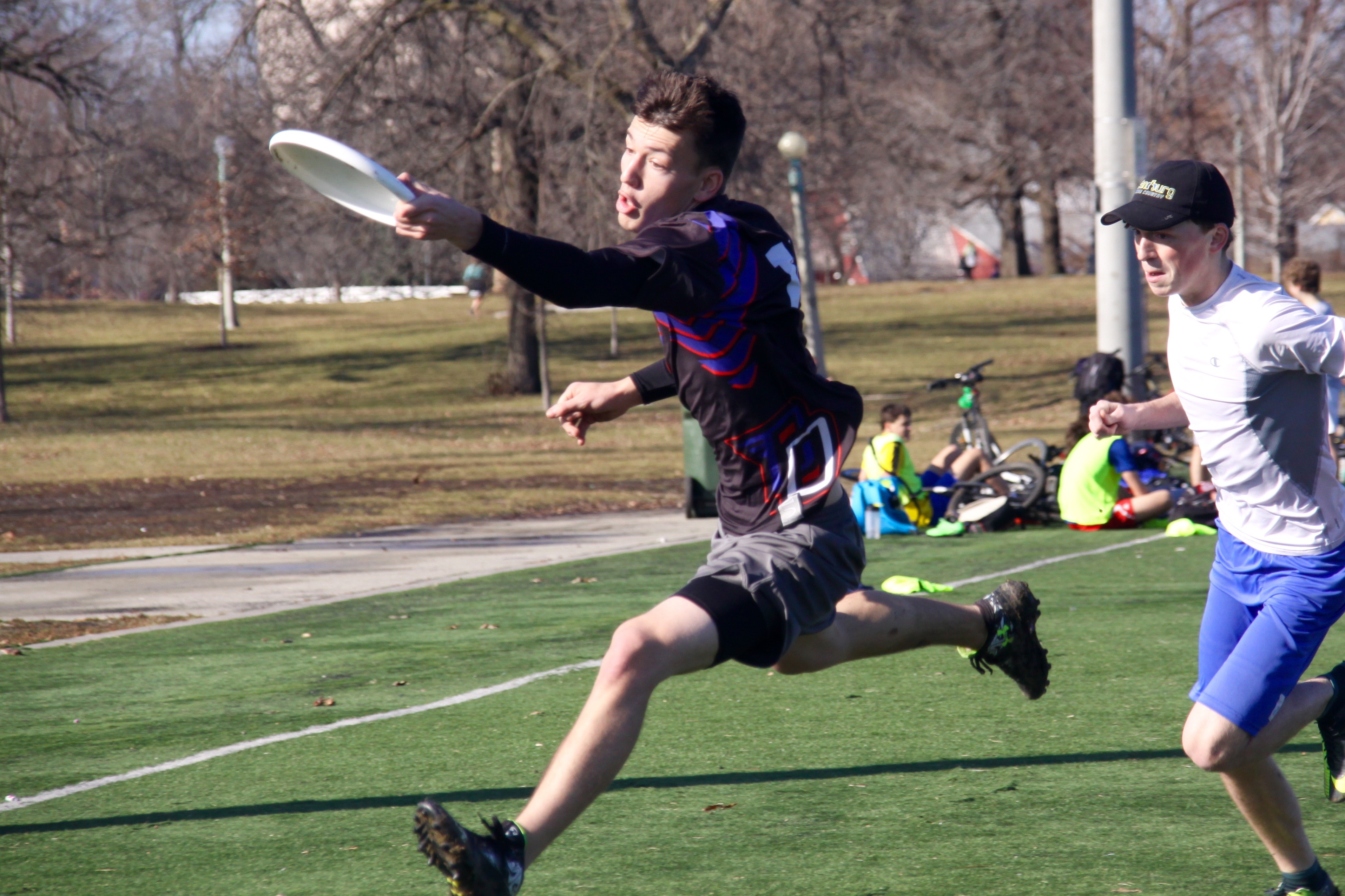 Jake Dremann catches a throw as Nick Carollo chases him down during a DePaul Ultimate Club practice on Jan. 21, 2017. (Photo/Ben Rains)