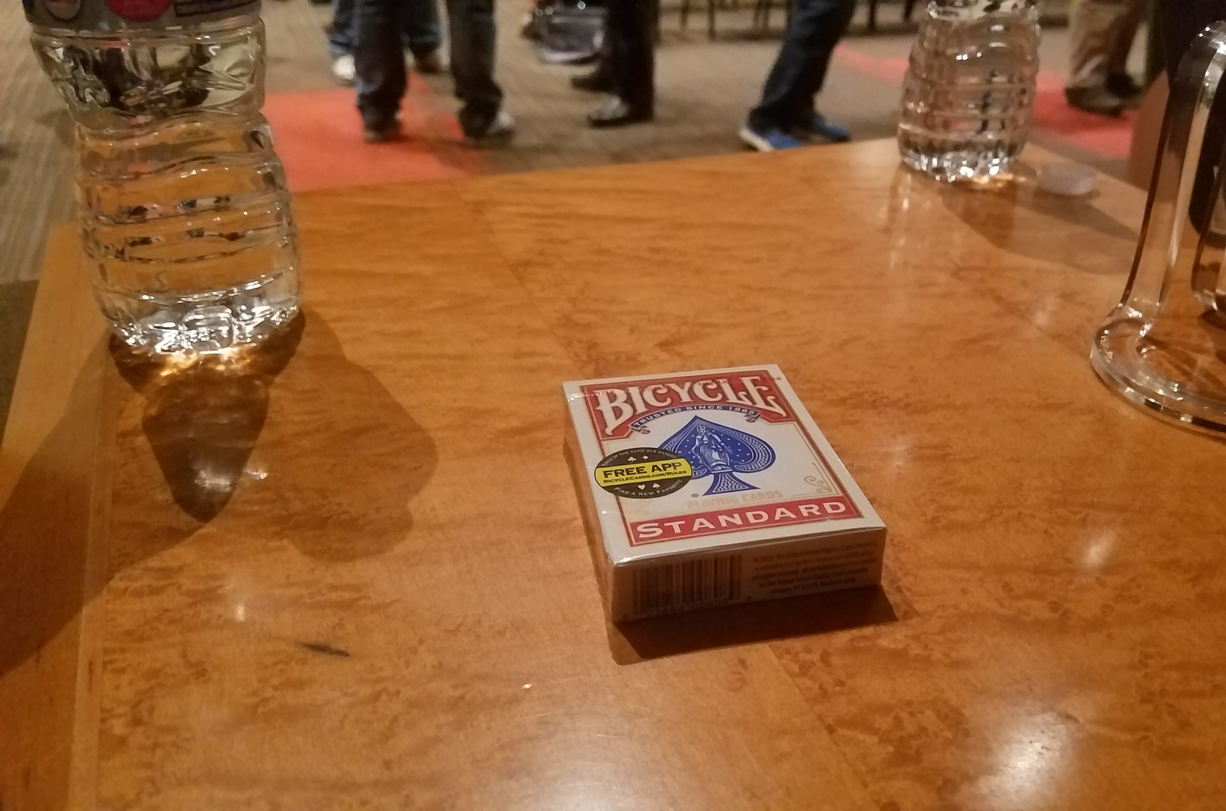 A pack of unopened cards between two water bottles on the stage where Ricky Jay spoke (Brendan Pedersen, 14 East)