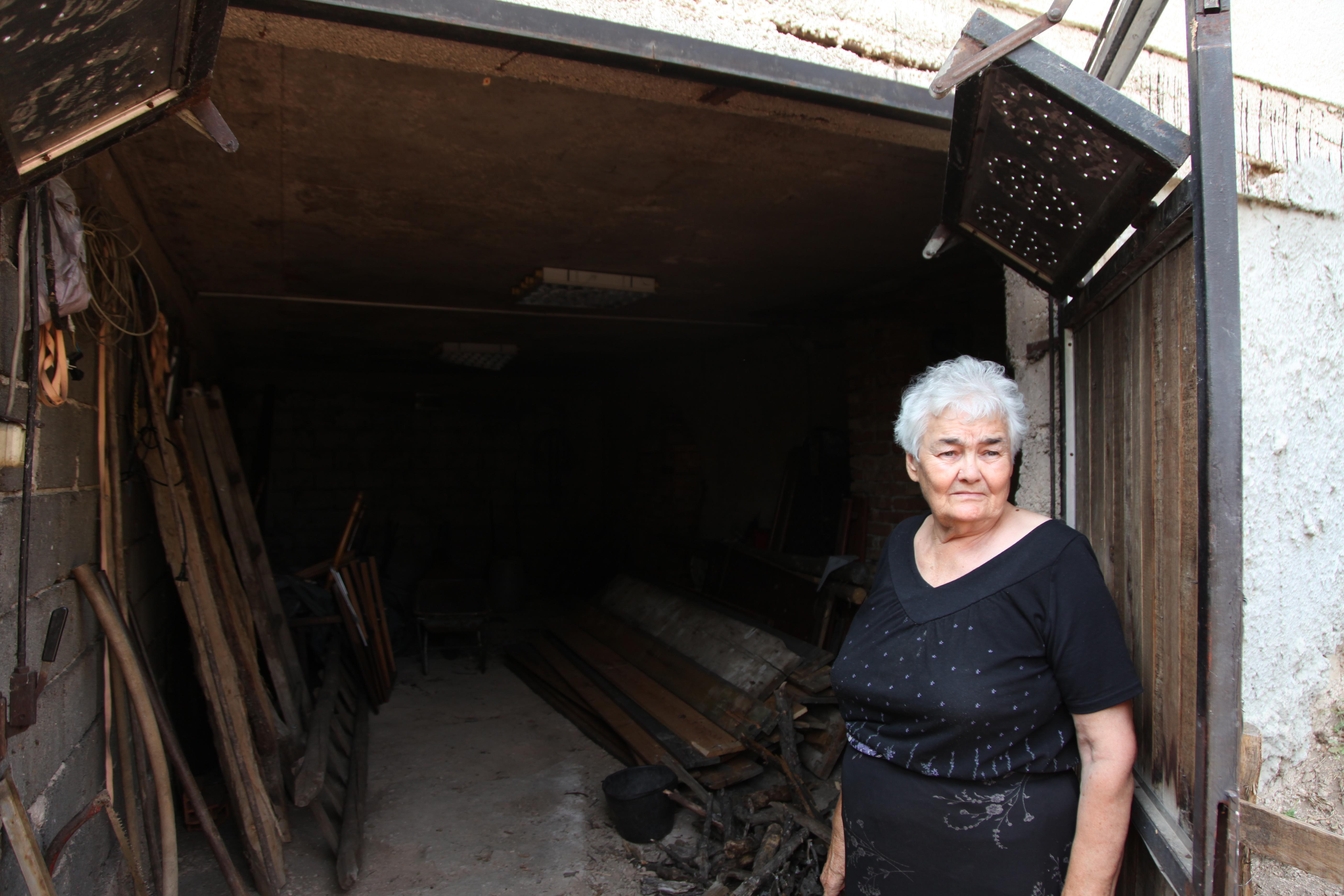 Kata Salipur, Salipur's grandmother, standing next to her basement.