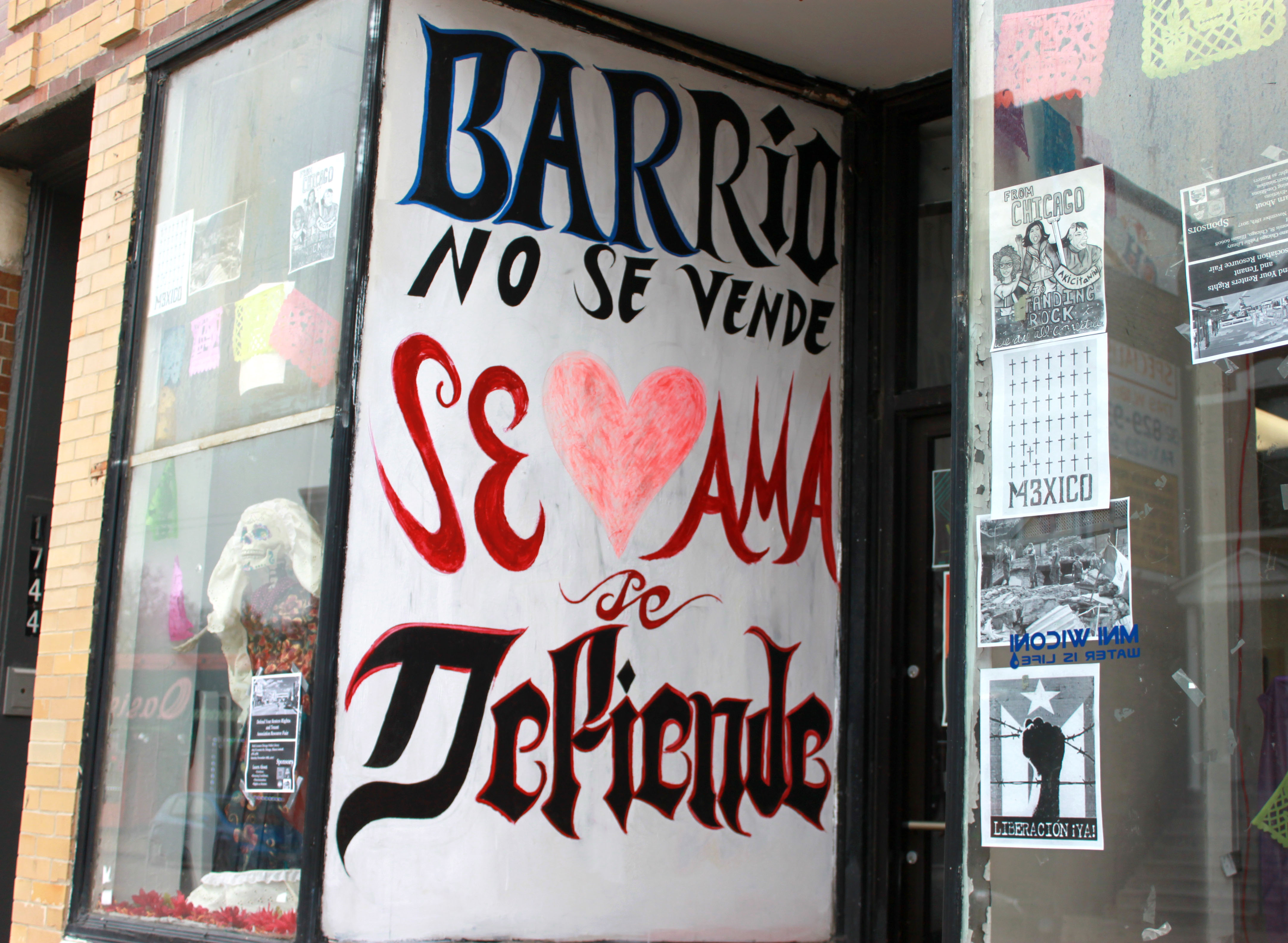 A sign on the outside of Pilsen Alliance. It reads 'Barrio does not sell you love it, you defend it'. (Jocelyn Nunez, 14 East)