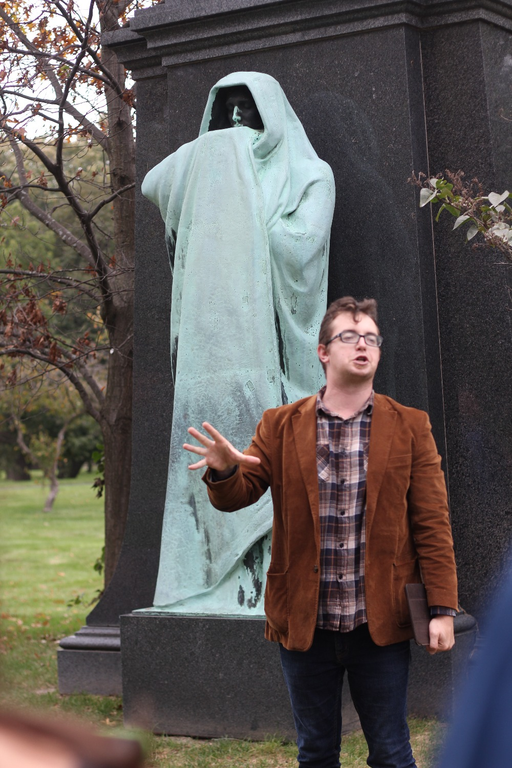 Adam Selzer stands in front of the Eternal Silence statue in Graceland Cemetery as he explains the monument's history to people on a tour of the cemetery. (Rachel Fernandez, 14 East)