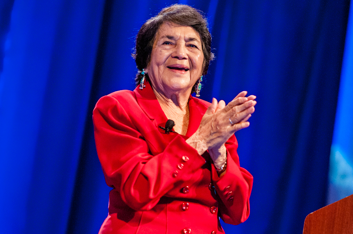 Photo of older Dolores Huerta clapping and wearing a red suit with turquoise earrings